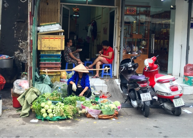 A lady selling green veg in the street