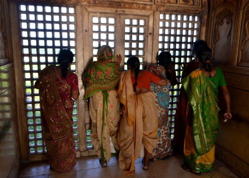 Ladies looking out of a criss crossed window to the Taj