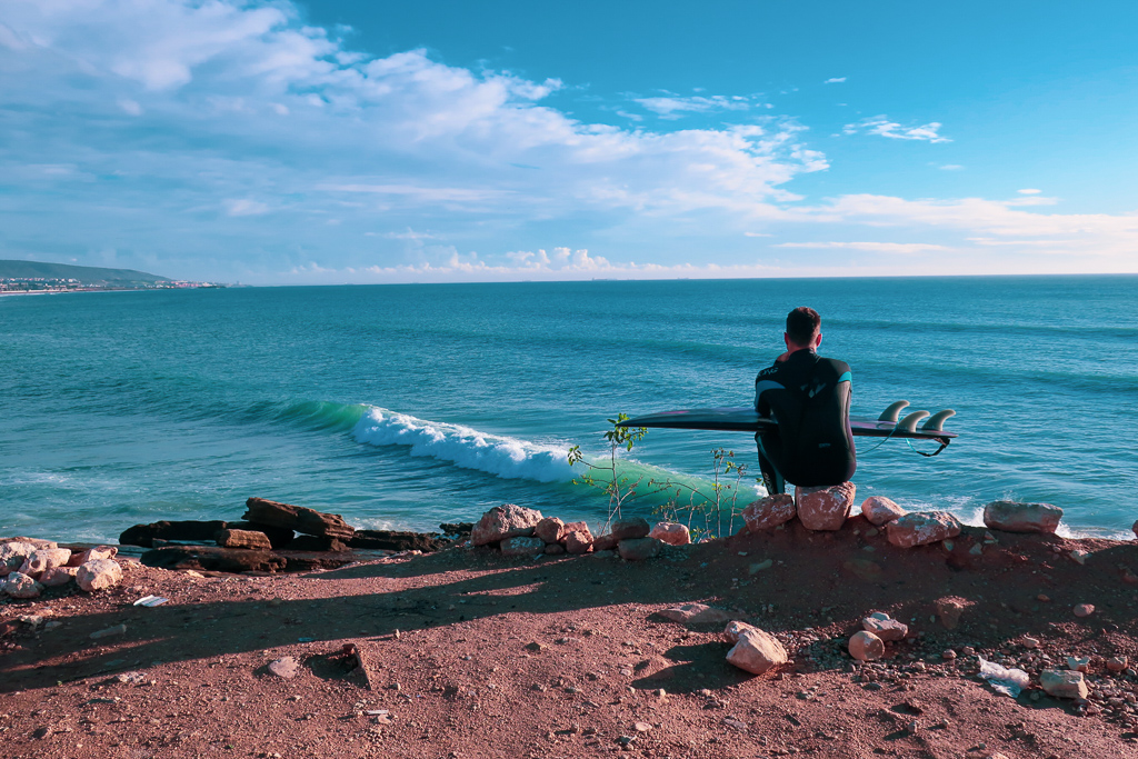 A man sits with his surfboard over looking the Atlantic in Taghazout