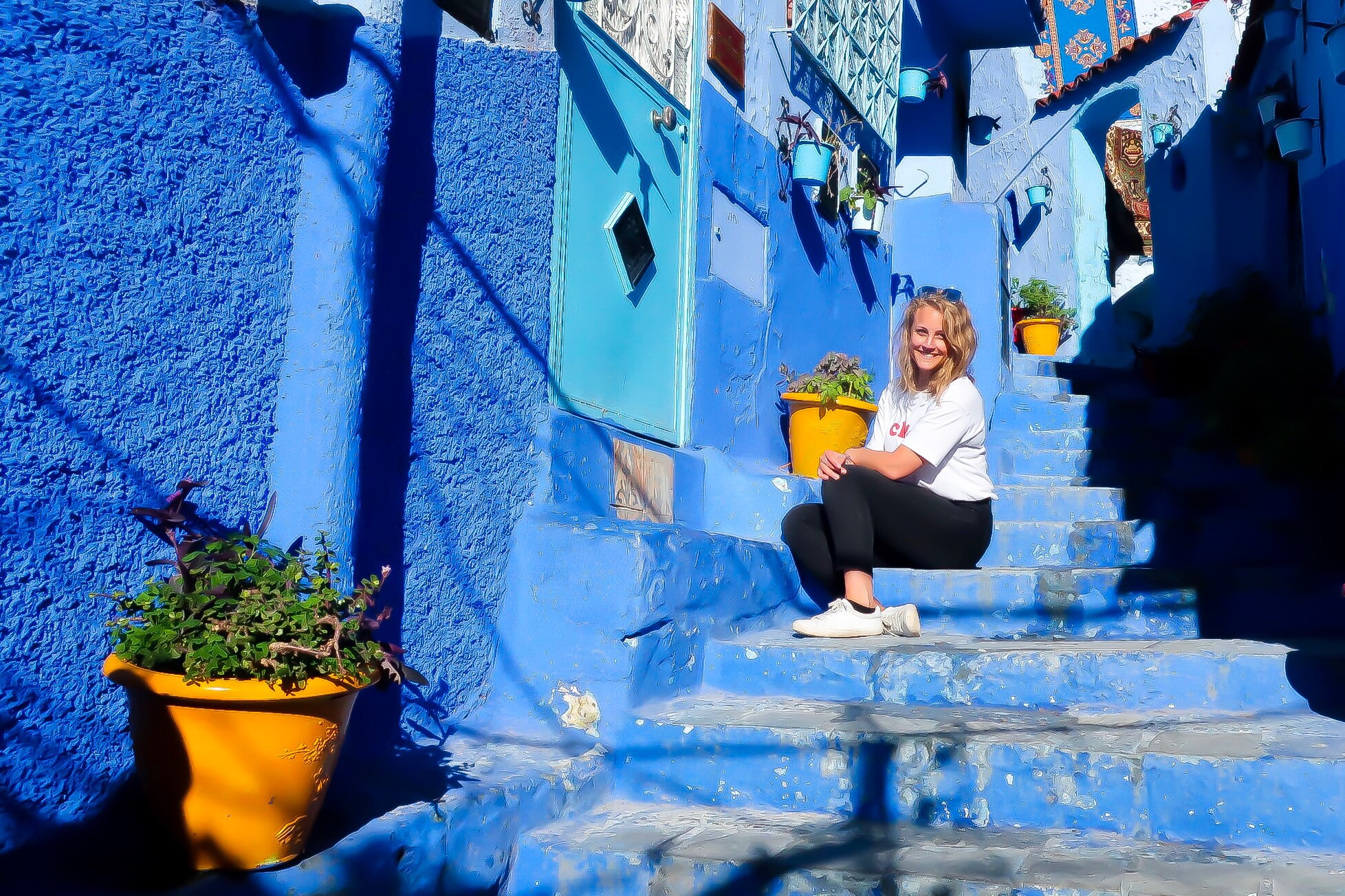 Me, dressed in white t-shirt and black jeans, sat in the sunshine in some blue stairs in Chefchaouen -