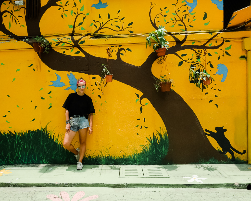 Me standing in front of the yellow street art in KL