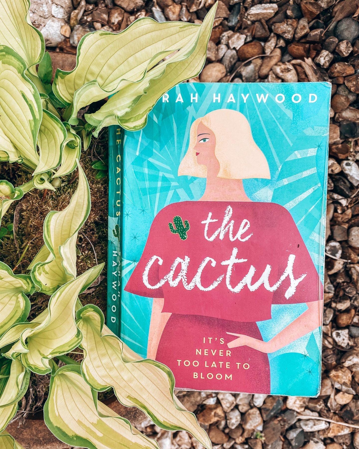 The Cactus book next to a green foliage