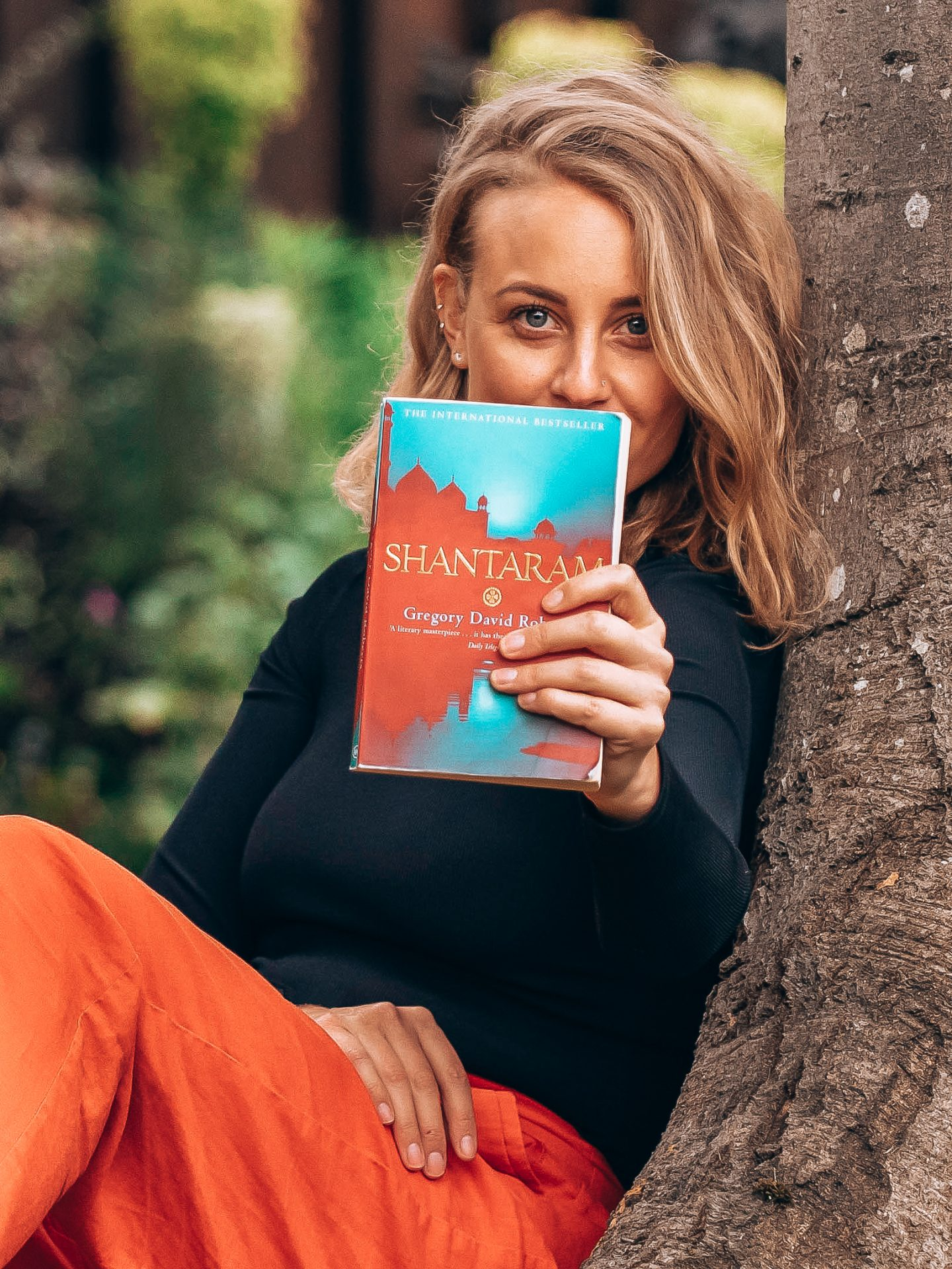 Shantaram Review - Sarah under the tree holding the Shantaram book in front of her
