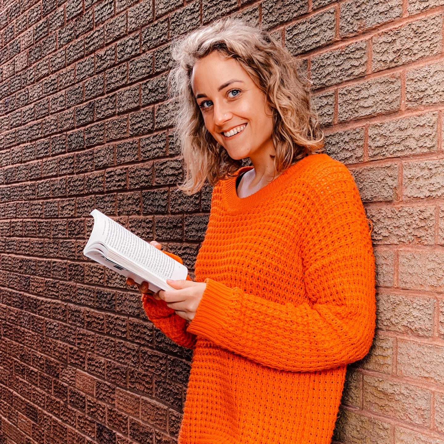 Sarah Smiling leaning against a wall