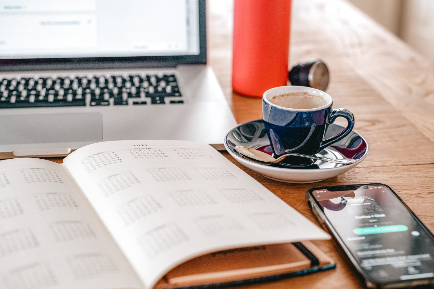 Coffee cup, diary and a laptop