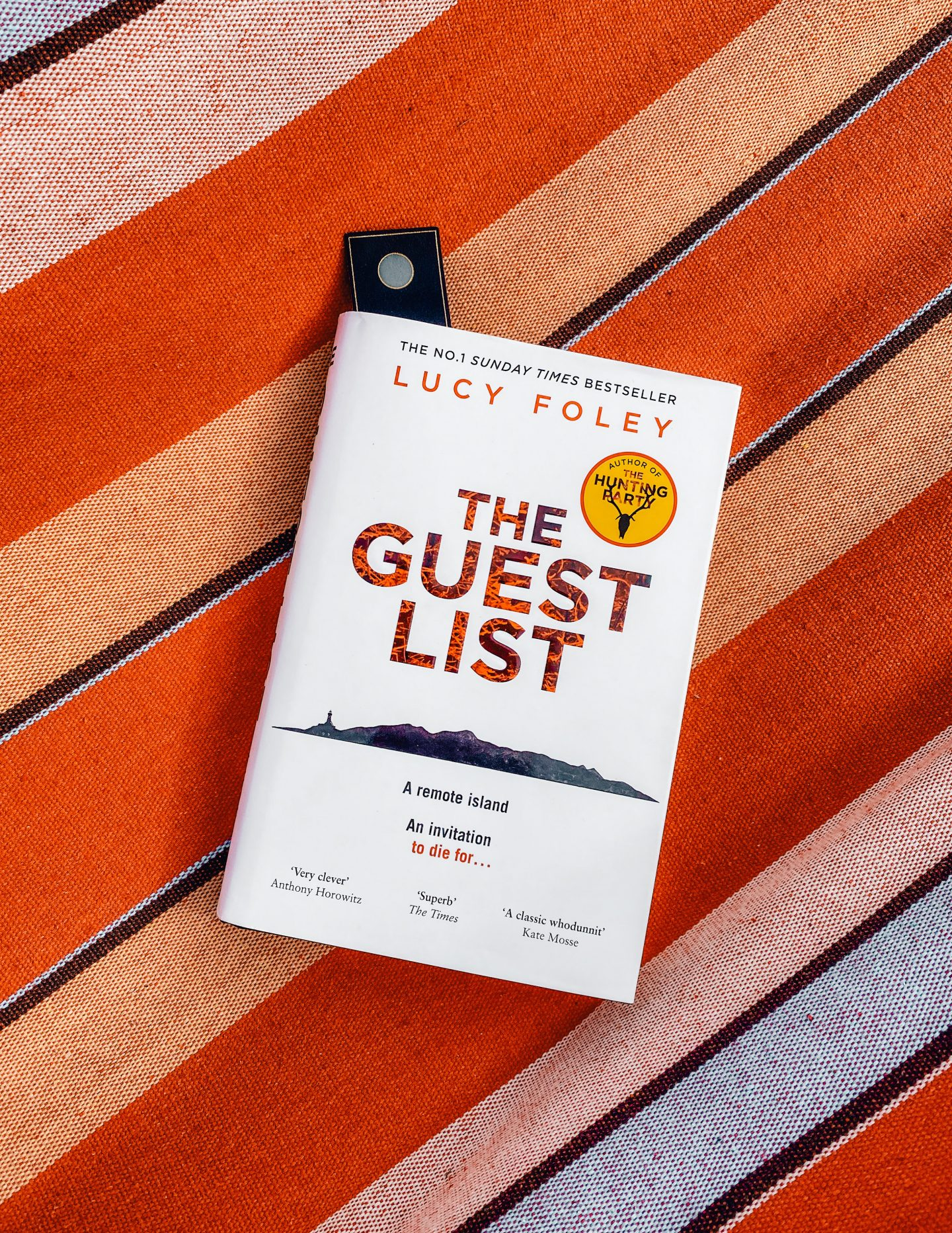 The Guest List book lays on an orange striped background